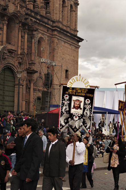 "A marching group sign that reads ""Urquillos - Sr Torrechayoc Comparsa Ccapac Dolla Myo Vicente Salgueron Y Esposa"""